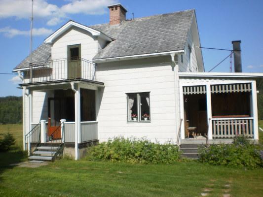 På sommaren - Husets utsida med veranda under tak.