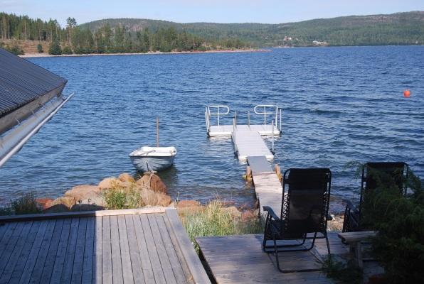 på sommaren - Brygga, båt och soldäck med solstolar.
