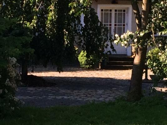 På sommaren - Entré med stensatt gårdsplan och glasdörr