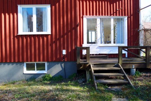 På sommaren - Husets baksida med veranda.