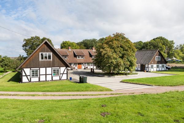 På sommaren - Det vänster huset av en U-längad Skånegård.