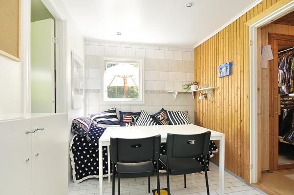 Vardagsrum - Allrum/sovrum. Här finns matbord för 4 personer, en kombinerad säng/soffa. En hylla med tv finns till höger utanför bilden.