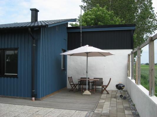 Terrass - uteplats med vindskyddande plastvägg till höger på bilden