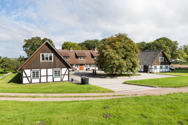 på sommaren - Det högra huset av en U-längad Skånegård.