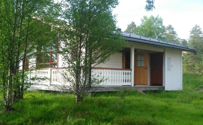 På sommaren - Stugans entré med altan och separat förråd med grill och utemöbler.