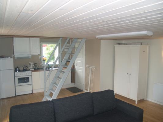 Kök - Öppen planlösning med kök och vardagsrum i ett. Trappa upp till sovloft. Dörr till toalett/dusch bakom trappan.