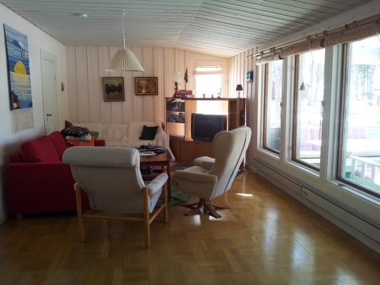 Vardagsrum - Vardagsrum med bäddsoffa, fåtöljer och TV. Fönster ut mot inglasade verandan och ned mot havet.