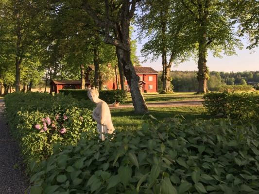 på sommaren - Huset ligger omgivet av en engelsk park med bl.a. lindar och blodbok på en liten halvö mot Mälaren.