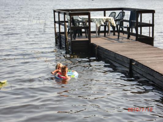 på sommaren - Badbrygga med fikabord i sjöviken.