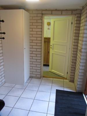 Interiör - Hall med klinker och plats för ytterkläder.