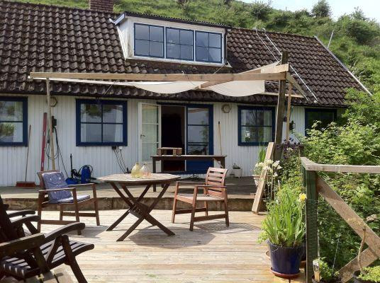 På sommaren - Framsidan av huset som vetter mot havet med en fantastisk terrass som sträcker ut mot havet.