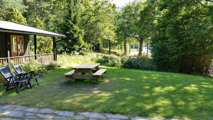 På sommaren - Husets uteplats, sjön i bakgrunden