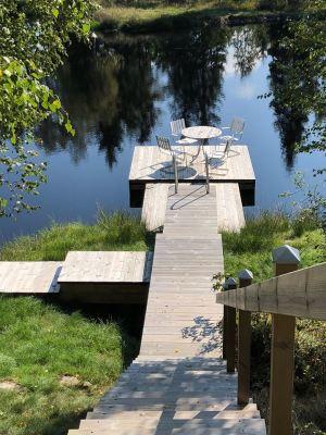 på sommaren - Brygga med möblemang med vacker utsikt över dammen