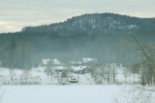på vintern - Gården från andra sidan sjön Barken