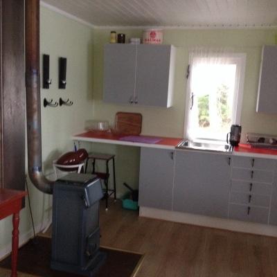 Kök - Här finns gasolkök, gasolkylskåp och en kamin att elda i om värme behövs. Innehåller enklare husgeråd.