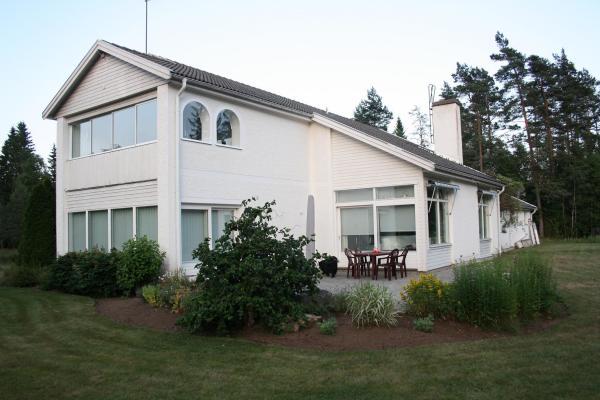 På sommaren - Exteriörbild med terass. Här ser man också den inbyggda balkongen på övervåningen