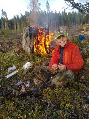 på sommaren - Kvällsfika med en värmande brasa i en tjärstubbe efter en dag i bärskogen.