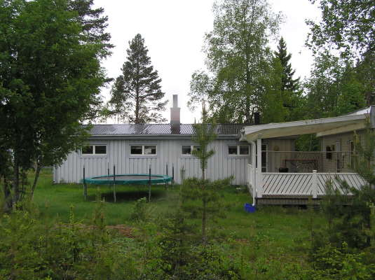 På sommaren - Altan med morgonsol på baksida av huset med skogen som granne.