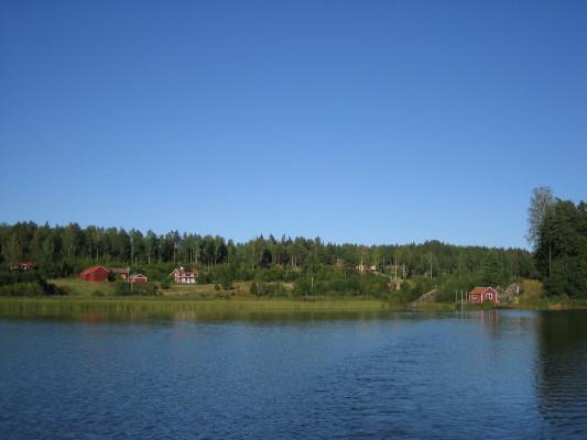 På sommaren - Malmviks Gård från sjön Skundern.