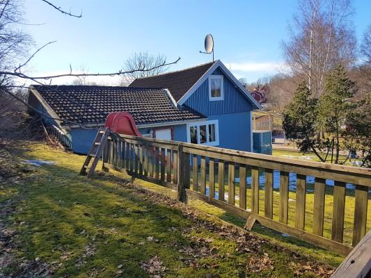 Ansicht Winter - Bullerbü auf einem Hügel gelegen, mit Rutsche und Schaukel im Garten.