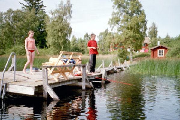 på sommaren - bryggan med bastun i bakgrunden