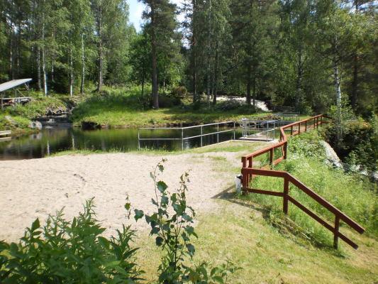 på sommaren - Kvarndammen för bad samt Likenäs-ån som skymtar i bakgrunden.