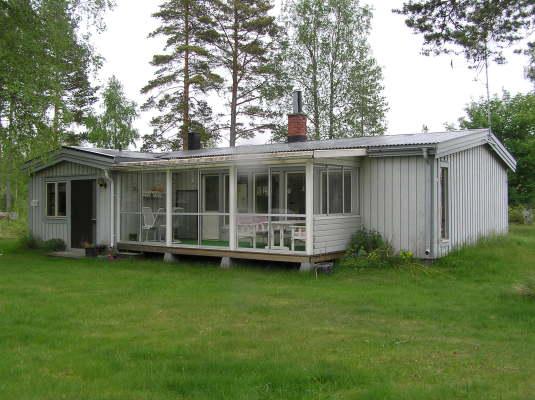 På sommaren - Framsida på stugan med inglasad veranda. Här finns härlig kvällssol. Infravärme gör att man kan sitta här även lite svalare kvällar.