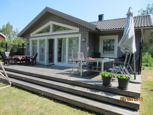 På sommaren - Fritidshusets framsida med inbjudande altandäck.