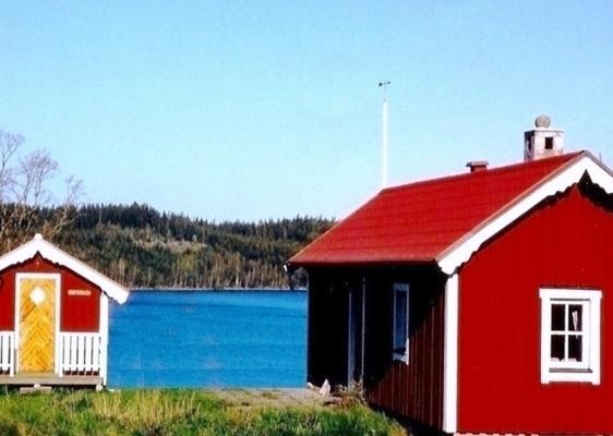 På sommaren - Huset och gäststugan sedda mot havets strand
