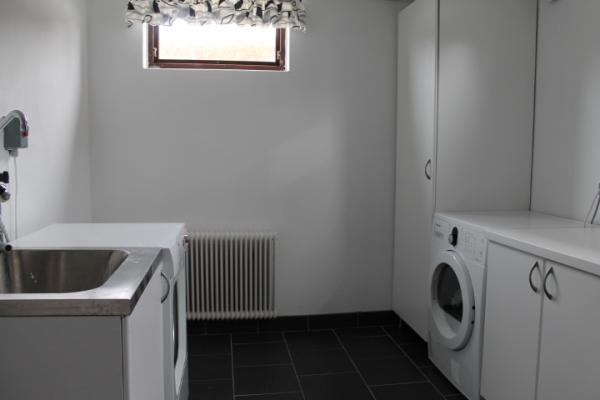 Interiör - Tvättstuga, med tvättmaskin, torktumlare, strykbräda och strykjärn.